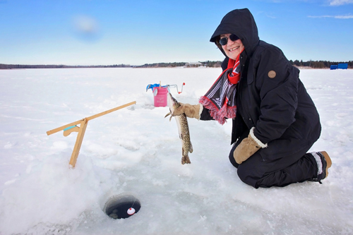 Older woman in dark snow suit holding a fish over an open hole in the ice
