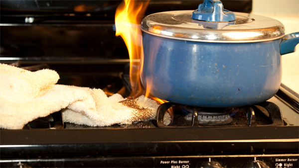Pot on fire on stove top