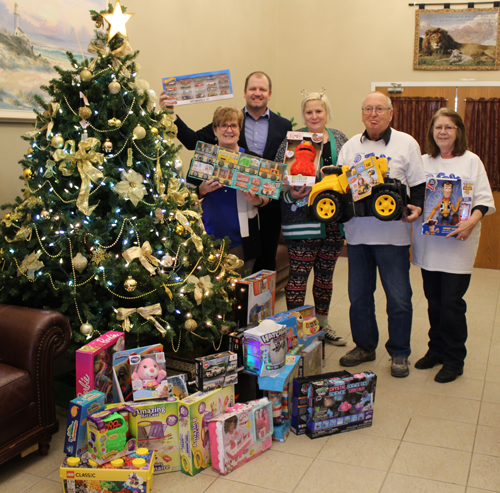 Mayor Margaret Quirk and Mike Hutchinson, manager of municipal law, with members of Optimist Club beside a Christmas tree with toys for children