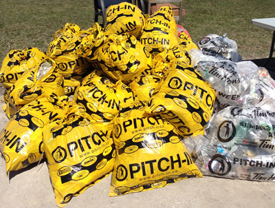 Yellow garbage bags full of trash with the words Pitch-In on the bags