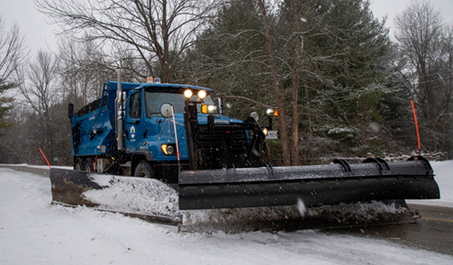 blue snowplow with black front blade clearing snow on the street